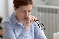 Femme fatiguée d'affaires tenant des verres faisant la pause pour le repos de yeux images libres de droits