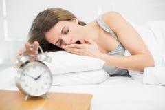 Femme fatiguée de brune arrêtant le réveil tout en baîllant Photos libres de droits