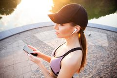 Femme fatiguée de forme physique suant faisant une pause écoutant la musique au téléphone après la formation difficile Écoute de  image stock