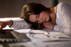 Femme fatiguée dormant sur la table de bureau la nuit images stock