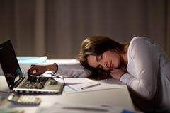 Femme fatiguée dormant sur la table de bureau la nuit photos libres de droits