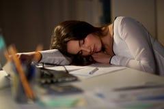 Femme fatiguée dormant sur la table de bureau la nuit image stock