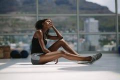 Femme fatiguée et épuisée se reposant après séance d'entraînement intense photos stock