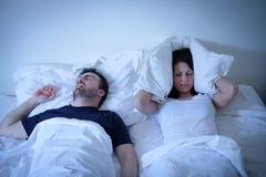Femme fatiguée et contrariée de son ami ronflant dans le lit Images stock