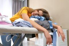 Femme fatiguée s'appuyant sur la planche à repasser avec des vêtements photo stock