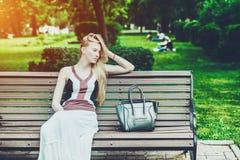 Femme fatiguée s'asseyant sur le banc du parc de ville Photographie stock libre de droits