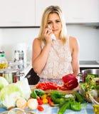 Femme fatiguée se penchant ses coudes à la cuisine Photographie stock libre de droits