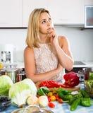 Femme fatiguée se penchant ses coudes à la cuisine Images stock