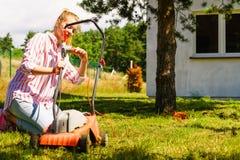 Femme fauchant la pelouse avec la tondeuse à gazon Photographie stock libre de droits