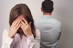 Femme fermant son visage avec le qurrel de couples de mains photographie stock