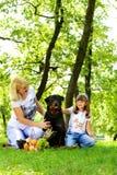 Femme, fille et chien sur l'herbe. Photographie stock