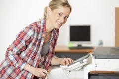 Femme fixant un photocopieur photo stock