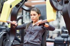 Femme fléchissant des muscles sur la machine de gymnase de presse de coffre image stock