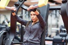 Femme fléchissant des muscles sur la machine de gymnase de presse de coffre images libres de droits