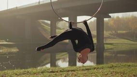 Femme flexible faisant les éléments acrobatiques sur le cercle aérien Brune accrochant en anneau clips vidéos