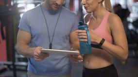 Femme flirtant avec son entraîneur de forme physique, parlant du programme de séance d'entraînement dans le gymnase banque de vidéos