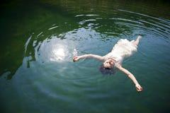 Femme flottant dans le lac Image libre de droits