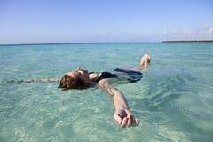 Femme flottant en mer Image stock