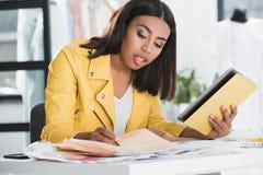 Femme focalisée à l'aide du comprimé numérique tout en travaillant dans le studio de conception d'habillement images stock