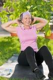 Femme folâtre aînée faisant le jour ensoleillé de sit-ups Photo stock
