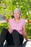 Femme folâtre aînée s'asseyant sur le couvre-tapis ensoleillé Image libre de droits