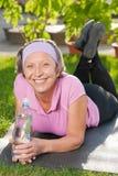 Femme folâtre aînée se trouvant sur le couvre-tapis ensoleillé Image stock