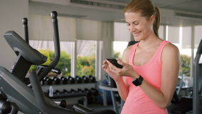 Femme folâtre active convenable faisant des exercices sur le velosimulator Utilisant son smartphone, transmission de messages ave banque de vidéos