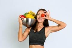 Femme folâtre dans les leggins tenant des fruits et le sourire femelle de modèle de forme physique de Veg image stock