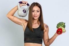 Femme folâtre dans les leggins tenant les fruits et le modèle femelle de forme physique de Veg avec la cloche de bouilloire images libres de droits
