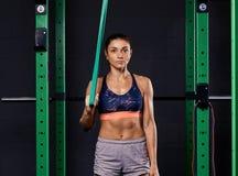 Femme folâtre habillée dans le soutien-gorge de sports et prises de shorts accrochant la courroie de suspension et regardant la c image stock