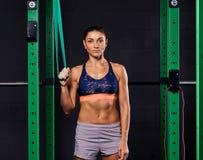 Femme folâtre habillée dans le soutien-gorge de sports et prises de shorts accrochant la courroie de suspension et regardant la c photos stock