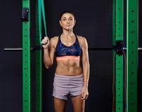 Femme folâtre habillée dans le soutien-gorge de sports et prises de shorts accrochant la courroie de suspension et regardant la c image libre de droits