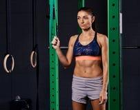 Femme folâtre habillée dans le soutien-gorge de sports et prises de shorts accrochant la courroie de suspension et regardant loin photographie stock libre de droits