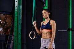 Femme folâtre habillée dans le soutien-gorge de sports et prises de shorts accrochant la courroie de suspension et regardant loin images libres de droits