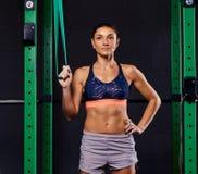 Femme folâtre habillée dans le soutien-gorge de sports et prises de shorts accrochant la courroie de suspension et regardant loin image libre de droits