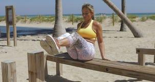 Femme folâtre s'exerçant sur la plage dans le gymnase banque de vidéos