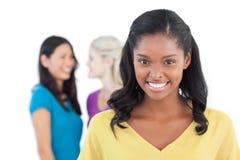 Femme foncée de sourire regardant l'appareil-photo avec deux femmes derrière elle images stock