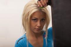 Femme forte d'ajustement s'exerçant dans un gymnase avec le sac de sable Amincissez la fille blonde dans le T-shirt bleu et le pa Image stock