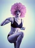 Femme forte de forme physique faisant un coup-de-pied de genou, mains dans Images stock