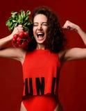 Femme forte de jeune sport assez gai posant avec des radis frais images libres de droits