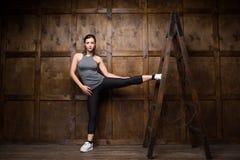 Femme forte employant une échelle en bois Images stock