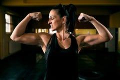 Femme forte musculaire montrant son corps après séance d'entraînement photos libres de droits