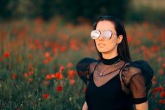 Femme fraîche avec les lunettes de soleil à la mode dans un domaine des pavots images libres de droits