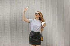 Femme fraîche avec les vêtements élégants prenant une photo elle-même Image stock