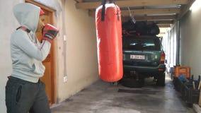 Femme frappant le sac de boxe dans le garage avec des gants banque de vidéos