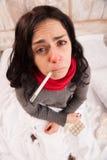 Femme frustrante se situant dans le lit avec des pilules image stock