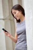 Femme futée d'affaires employant l'APP sur le smartphone Image stock