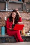 Femme futée d'affaires travaillant sur son ordinateur portable à la maison dans la cuisine Image libre de droits