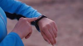 Femme futée de montre à l'aide du bouton émouvant de smartwatch dehors banque de vidéos