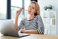 Femme futée gaie mordant son crayon Photo libre de droits